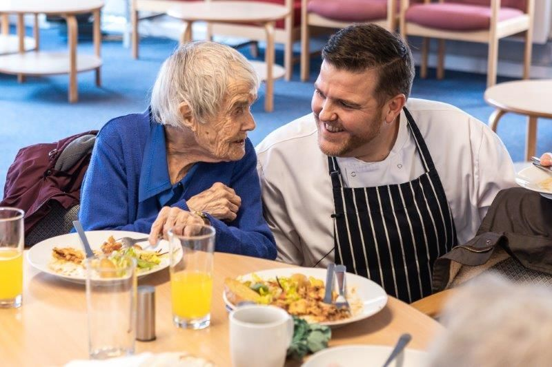 Man in a chefs uniform chatting to a care home resident