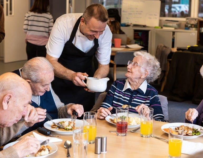 Chef pouring gravy for care home residents