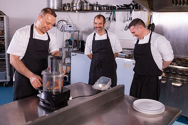 three chefs using a food processor in a resteraunt kitchen