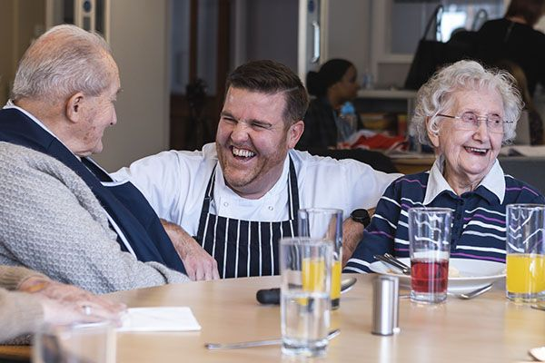 A chef sitting between 2 care home residents and laughing