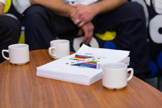 Closeup of cups and a brochure on a coffee table