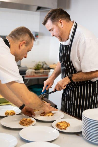 two chefs in a commercial kitchen, serving several plates of food