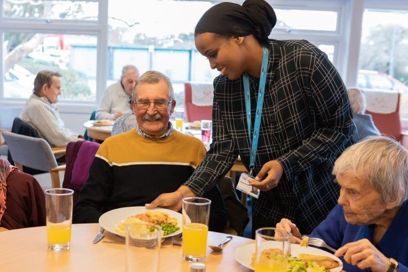 A woman serving food to residents in a care home