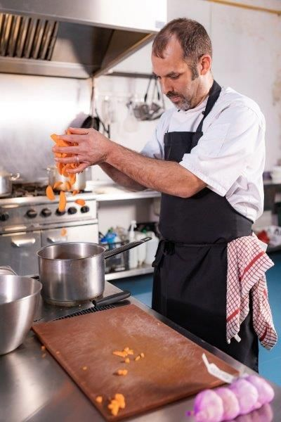 Chef in a restaurant kitchen dropping carrots into a saucepan