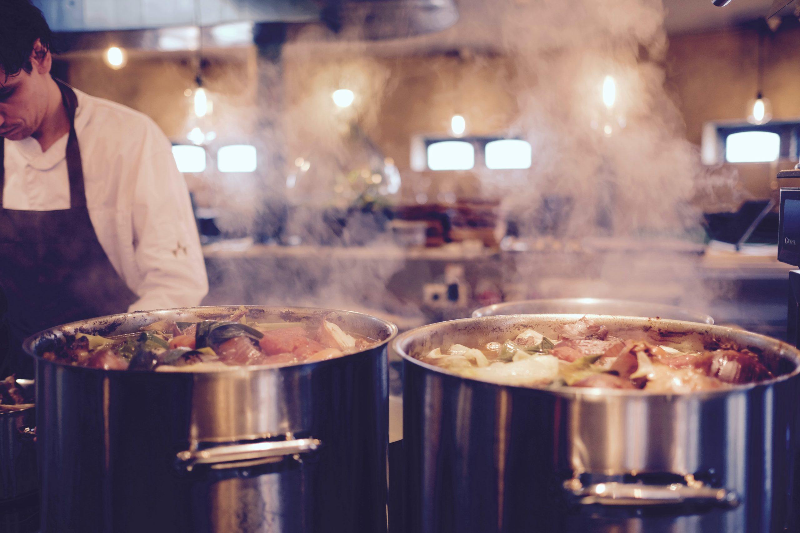 Commercial saucepans full of boiling veg in a restaurant