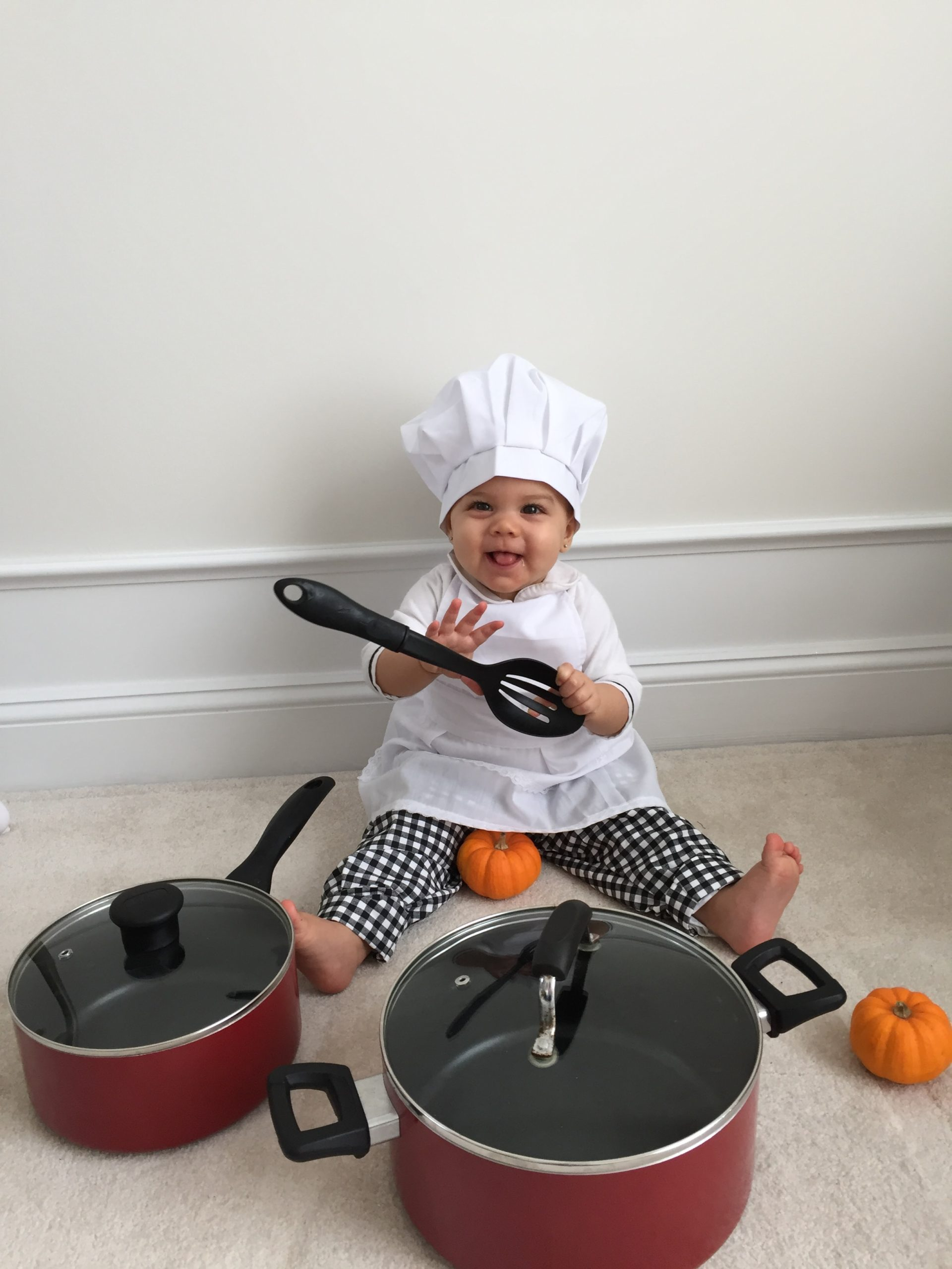 Young child in a chef's outfit, playing with kitchen utensils